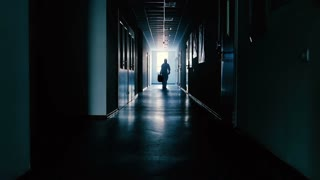 The scientist in protection suit with bag in hand is going through a corridor