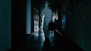 The scientist in protective suit and with bag going through the corridor