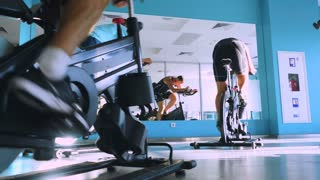 The sportsmen training on the exercise bikes in the gym