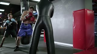 The team trains at a boxing punching bag