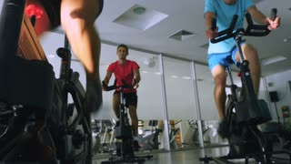 The trainer and young sportsmen are training on the exercise bikes in the gym