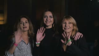Three smiling women waving hands and send a kiss into the camera