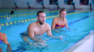 Three young people doing water exercises on the trainers in the swimming pool
