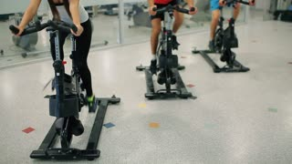 Two attractive men and beautiful woman is cycling in the gym