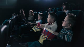 Two boys are eating popcorn in the cinema