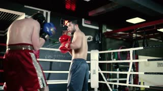 Two guys fight in the boxing hall