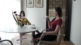 Two women sitting at a table in a hotel room