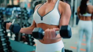 A girl trains the muscles of the arms with dumbbells
