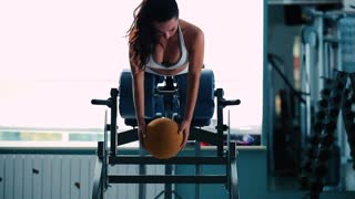 A girl trains the muscles of the back in gym