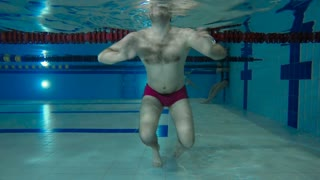 A man dip under the water in swimming pool