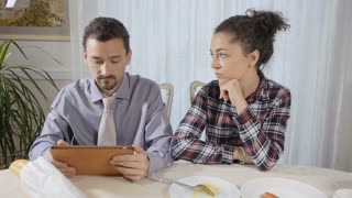 A man does not pay attention to his wife reading the news in the tablet