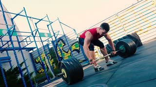 A muscular guy try to raise up the barbell on the sports ground