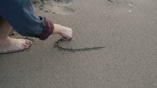 A woman's hand draws on wet sand