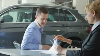 A young man signing papers at an automobile store