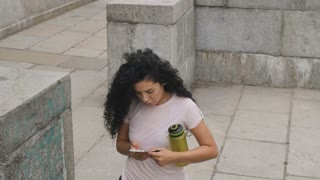 Active lady with phone in hands walks upstairs outdoors