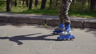 Adorable boy riding on roller skates in summer park