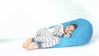 Adorable cute children sleep on bean bag at white background