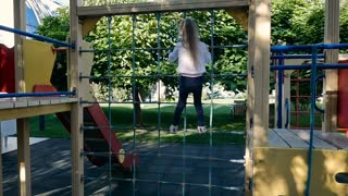 Adorable little girl clims on the rope at playground