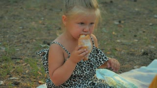 Adorable little girl eat croissant in park