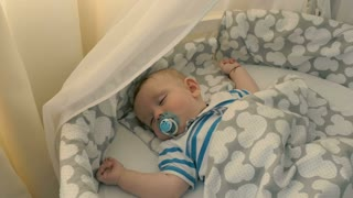 Adorable little kid with dummy is sleeping in a crib