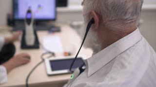 Adult man with a gray beard passes the test for hearing