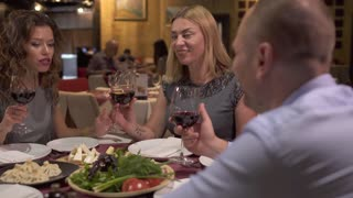 Adult people relaxing at restaurant drinking red wine