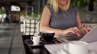 Adult woman in grey dress typing laptop sitting at table in restaurant