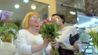 Adult woman learn to make flower bouquet under supervision of florist