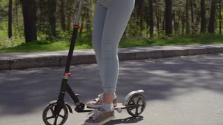 Adult woman rides on kick scooter near the children on roller skates in park