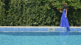 Amazing brunette with cocktail in blue dress fall in swimming pool in slowmotion
