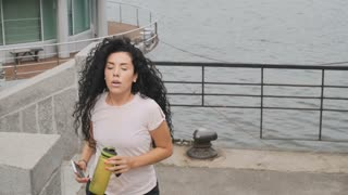 Athletic lady runs upstairs near the river