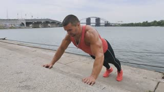Athletic man pushes-up near the river