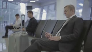 Attractive businessman sits comfortably and waits a boarding on plane
