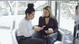 Attractive businesswomen dicussing something looking at phone