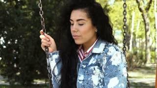 Attractive girl in jeans jacket swings on swing in park