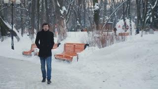 Attractive man has a promenade in the winter park