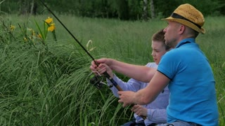 Attractive man teaching his son to fish with rod