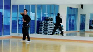 Attractive man training the wushu in the gym