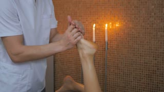 Attractive masseur massaging the girl's right foot in the spa