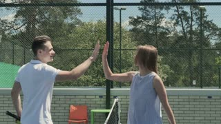 Attractive people give five to each other at the end of tennis game