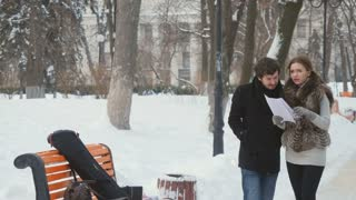 Attractive people have a conversation in the winter park