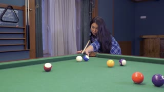 Attractive woman learns to play billiard