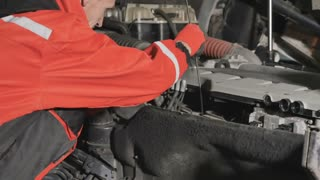 Auto mechanic checks the oil level in engine of truck