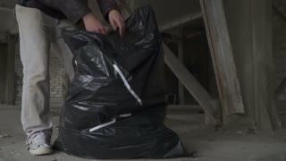 Bald homeless searches something in garbage bag