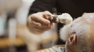 Barber applies shaving cream on face of old man and prepares skin to shaving