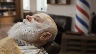 Barber covers face of mature man with a hot towel