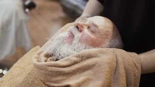 Barber steam up the face of mature man with hot towel before shaving