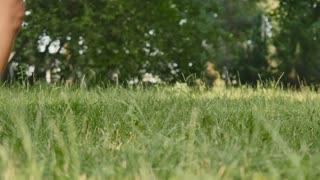 Barefoot woman jumps on green grass