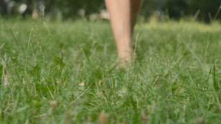 Barefoot woman walks on green grass