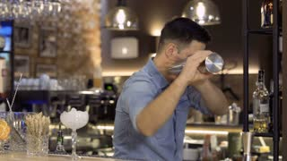Barman shakes cocktail in shaker